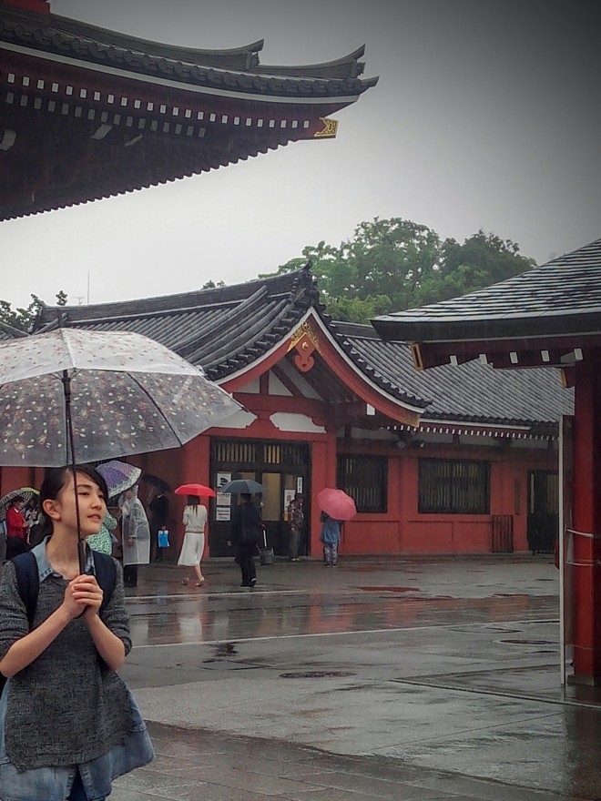 female temple visitor with umbrella tokyo japan